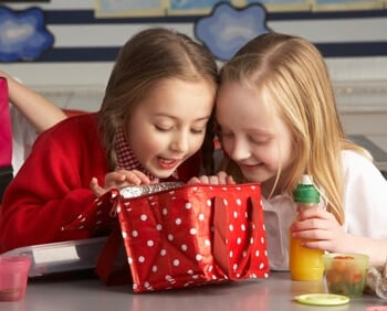 two girls looking into a red lunchbox with white polka dots.