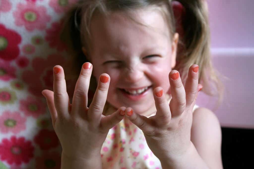 little girl with nail polish on her fingers