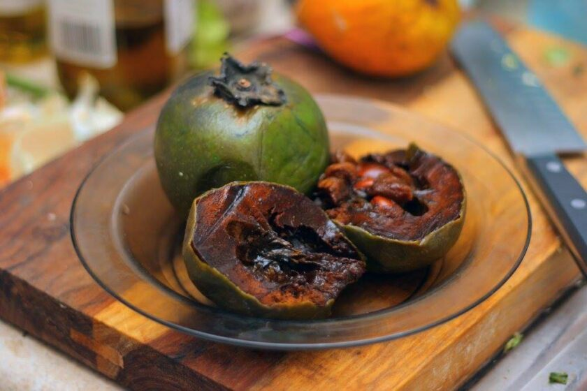 sapote sliced open on a glass plate