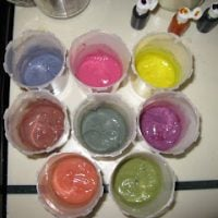 eight cups full of homemade non toxic finger paints in bright colors