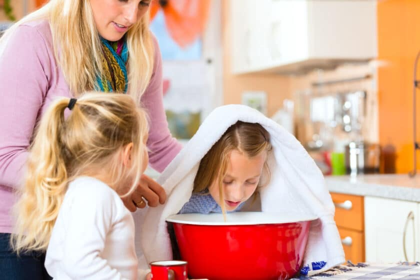mother and daughter helping other daughter hold a towel over her head to inhale steam from a red bowl