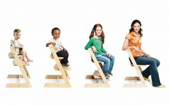 4 Tripp Trapp chairs with baby, kid, teen and adult sitting on them