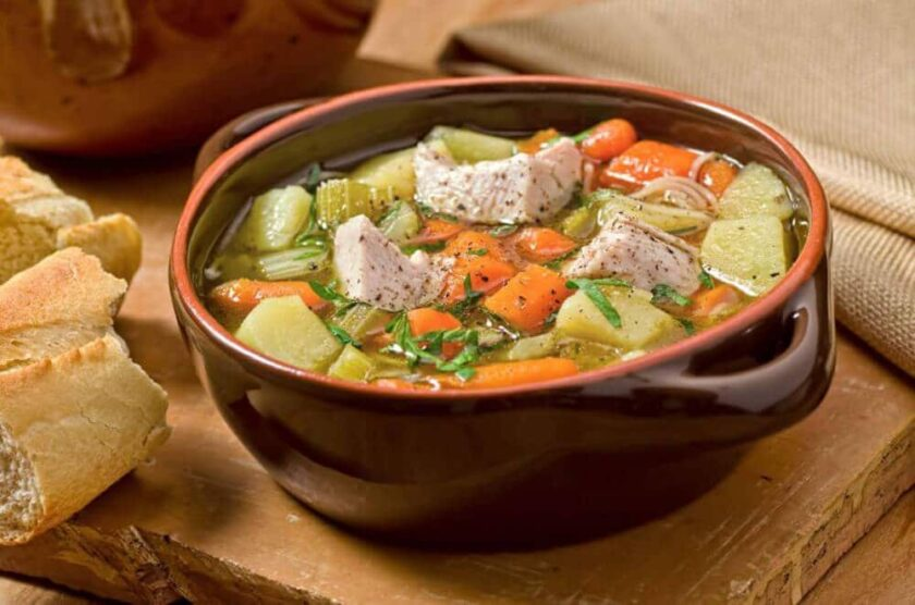 brown ceramic bowl full of turkey soup with root vegetables