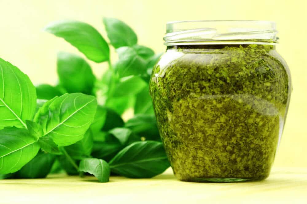 jar of pesto next to basil leaves