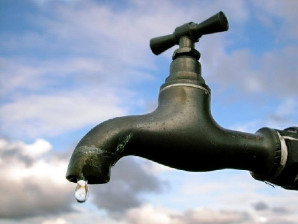 leaky outdoor spigot against a cloudy, blue sky