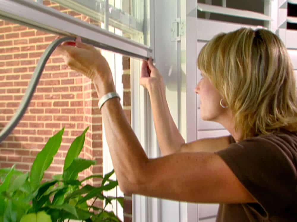 woman applying weatherstripping to a window.