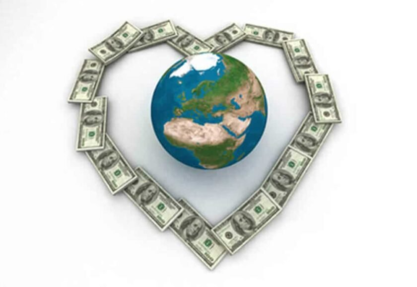 globe surrounded by dollar bills in the shape of a heart