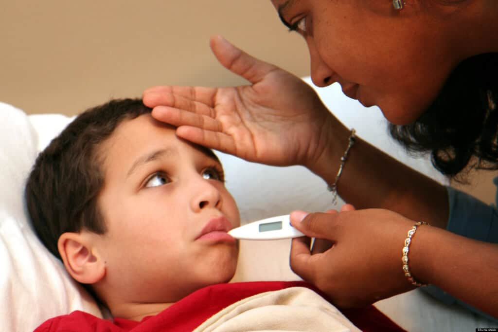 mother taking child's temperature with a thermometer