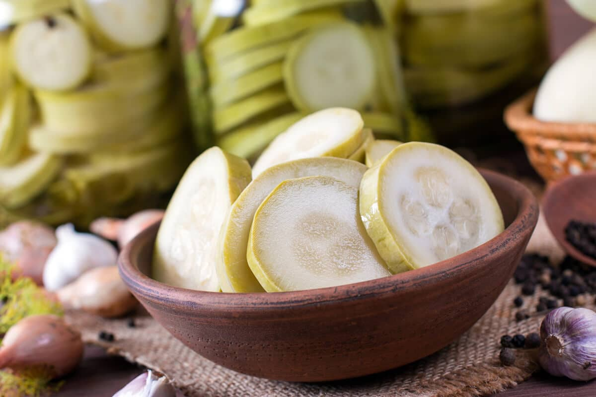 zucchini pickles in a bowl with jars of pickles behind
